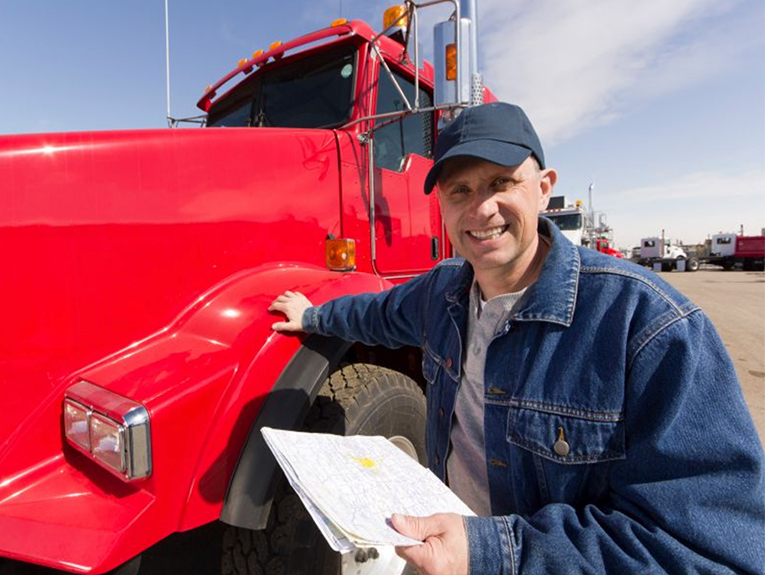 trucker standing next to red truck