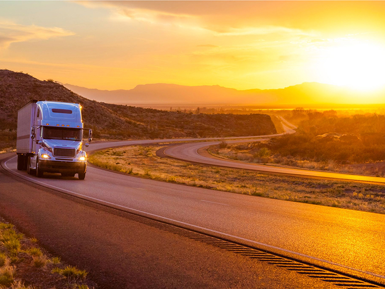truck driving on road during sunset