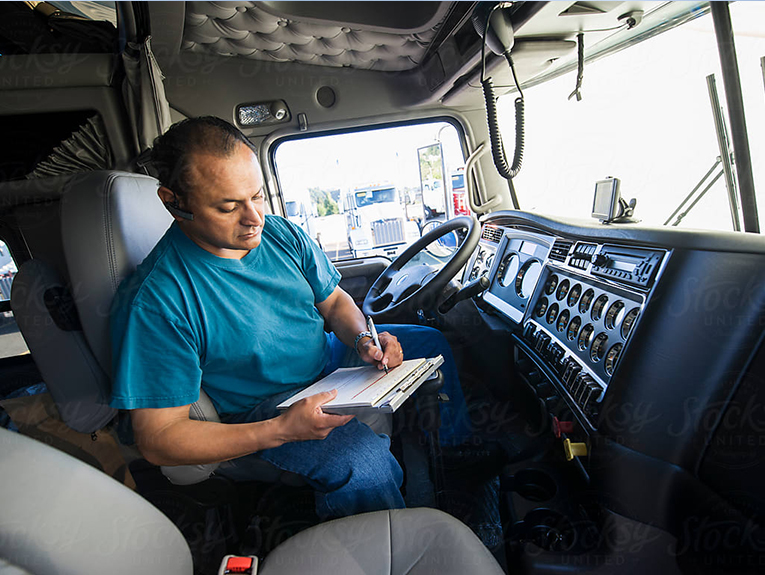 Man in teal shirt working on a clipboard inside a semi truck