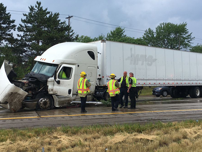 Crashed white Semi Truck with workers in front of it