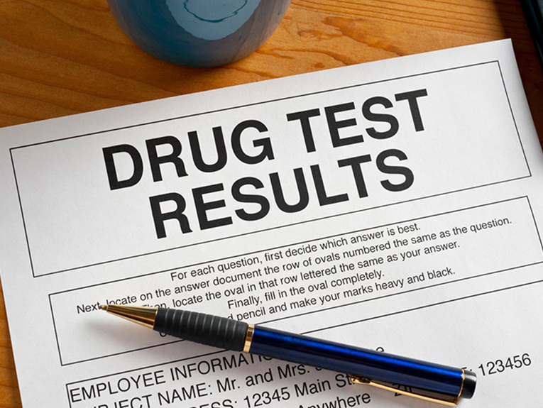 Paper with the words drug test results on the top. With a pen on the paper