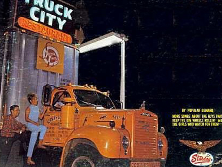 Old orange truck with truck city sign over it