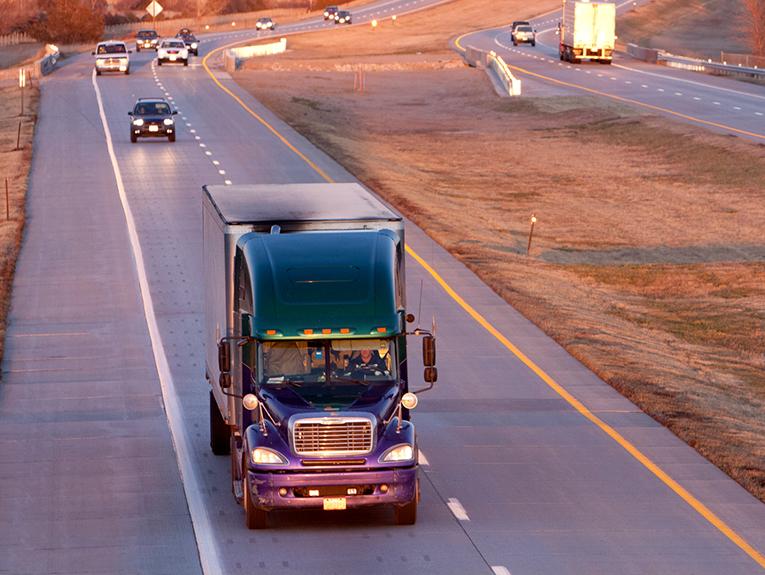 Semi truck driving into sunset