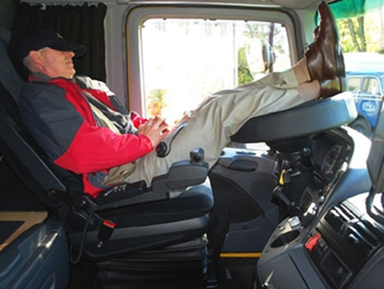 Man in red jacket sleeping in semi truck cab, with feet on wheel