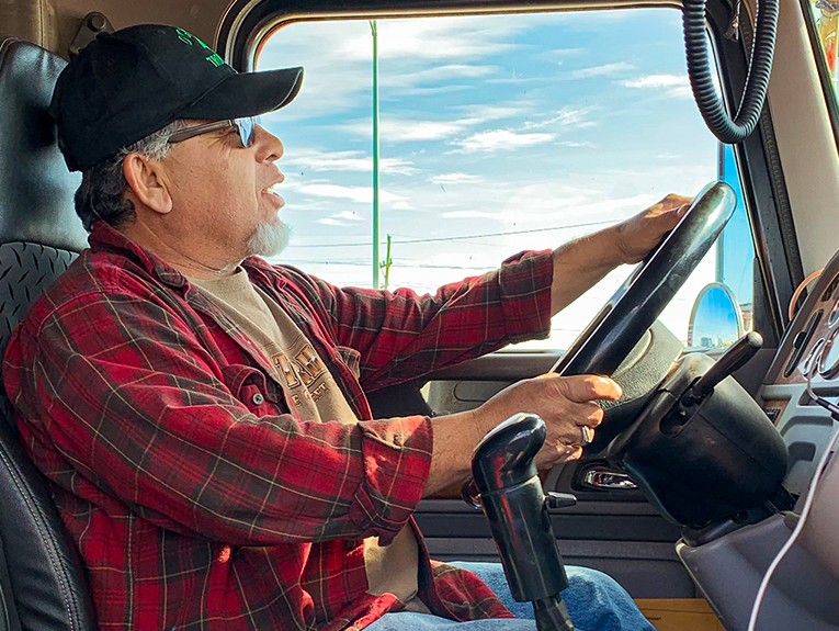Older man in red flannel inside cab of semi truck