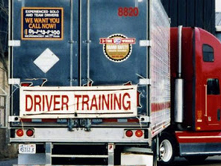 The back of a semi truck with the words driver training on back