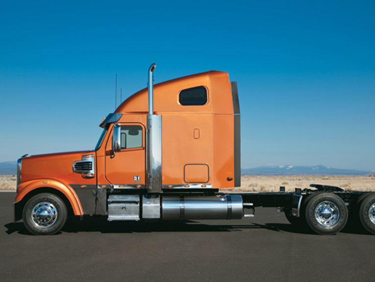 orange truck in front of ocean