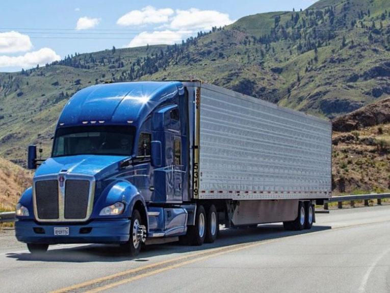 Blue Truck driving past hills