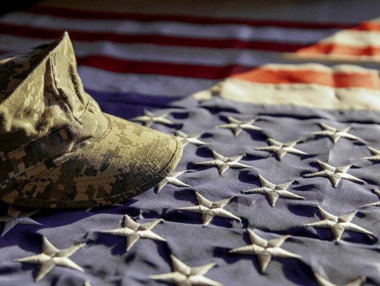 American flag with army hat laying on top