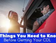 guy in a hat and sunglasses looking out of his red semi truck - 3 things you need to know before getting your CDL